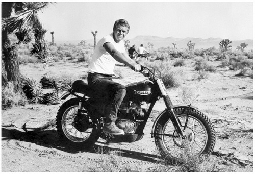 By gp314 (steve-mcqueen-bud-ekins-triumph-desert-motorcycle-racing), [CC BY-NC-SA 2.0 (https://creativecommons.org/licenses/by-nc-sa/2.0/)], via Flickr
